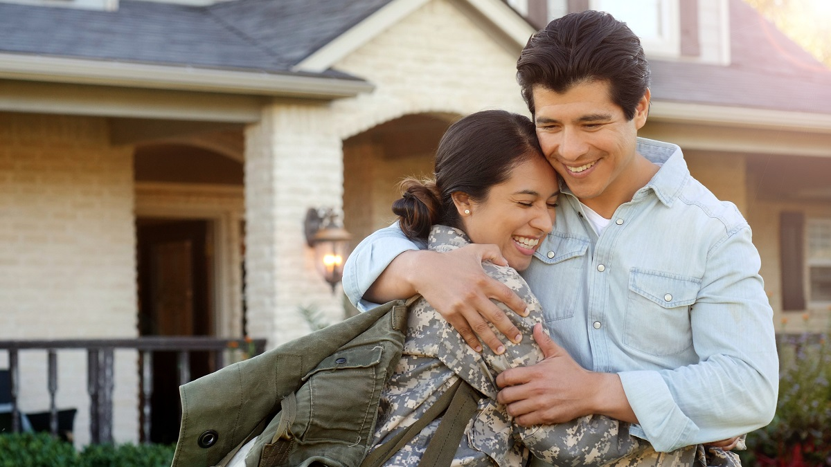 Couple hugging in front of their home.